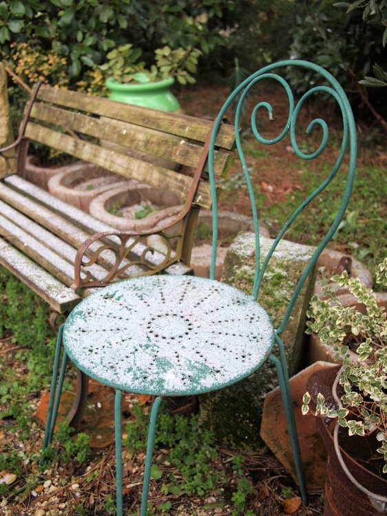 Winter garden chair covered with frost